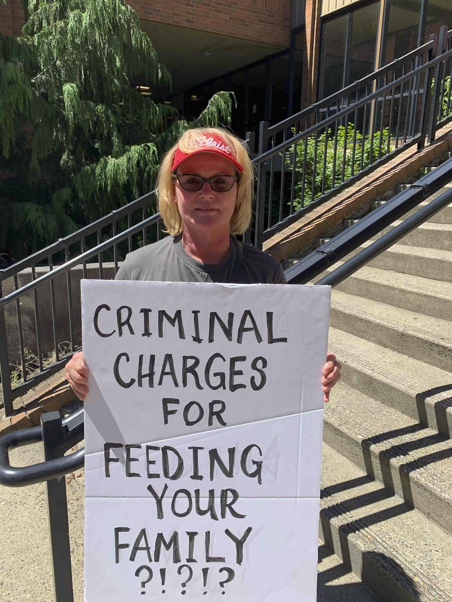 Kelly Carroll poses with a sign outside of the Clark County Courthouse in the weeks after she was charged with violating the governor's order by opening her pet grooming business during Phase 1 of the Safe Start Washington reopening plan. Photo courtesy Kelly Carroll
