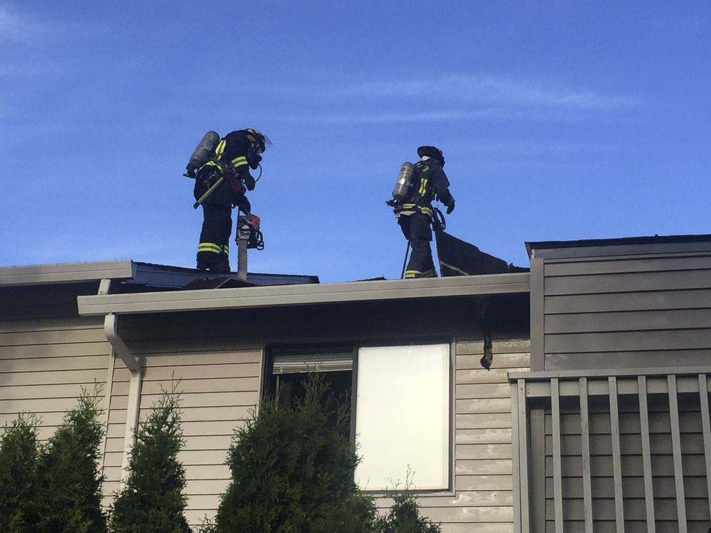 A Vancouver ladder truck crew went to the roof to reach an area of the attic that was difficult to access from below. Photo courtesy of Vancouver Fire Department