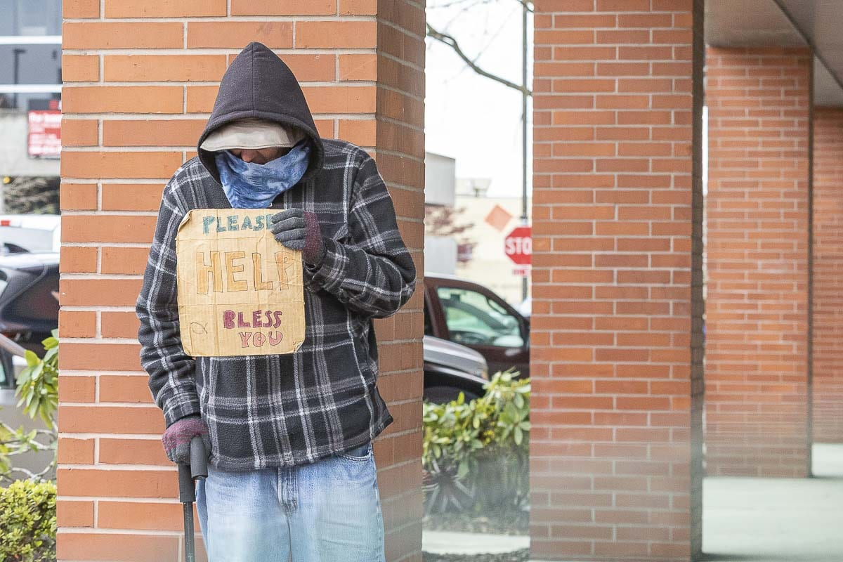 A homeless man holds a sign in Vancouver last March. Photo by Mike Schultz