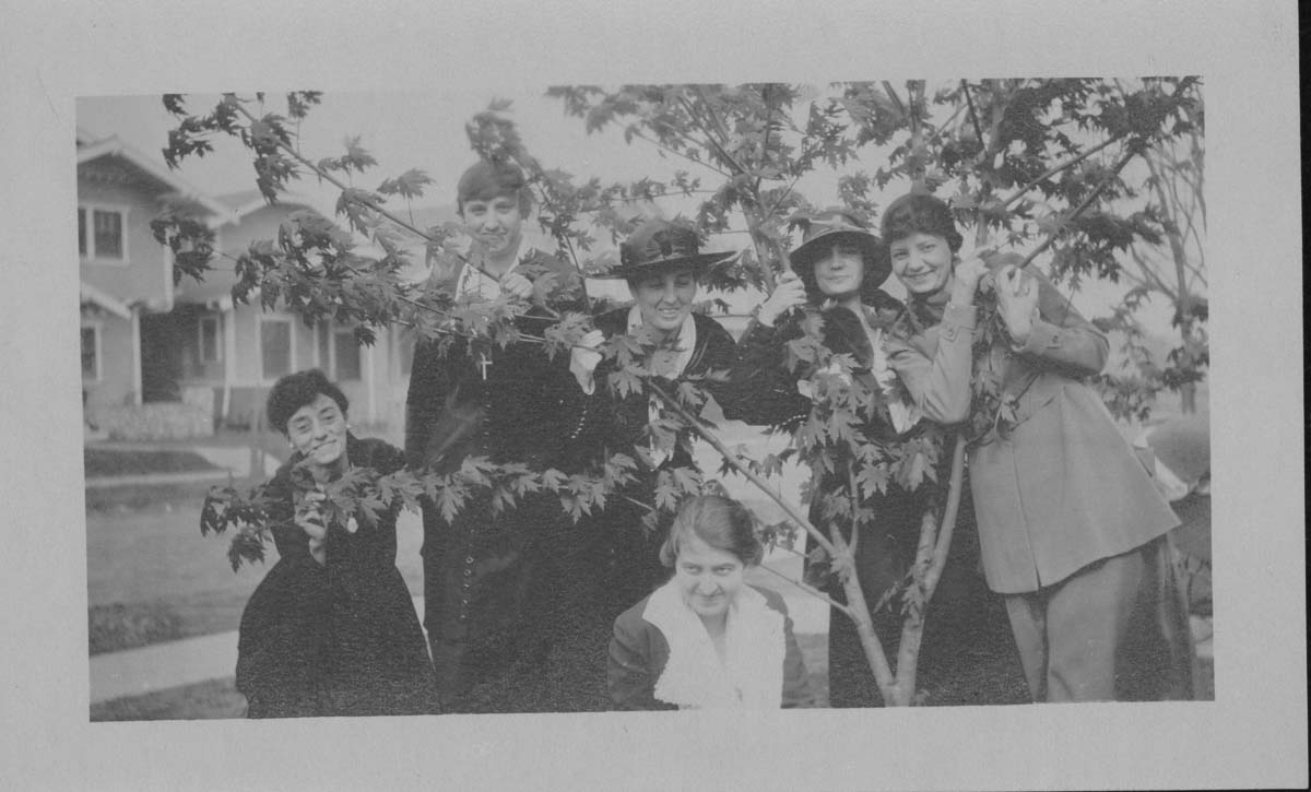 Snapshot of a group of six women posing through tree branches in the front yard of a home on a residential street (undated). Photo courtesy of CCHM Digital Collection