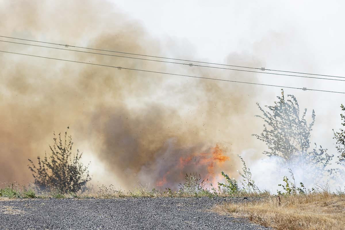 Flames burn through brush west of Fruit Valley Road in Vancouver on Tuesday. Photo by Mike Schultz