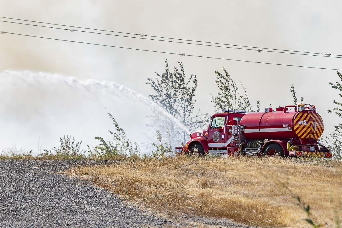 A Vancouver Fire water tender fights a grass fire along Fruit Valley Road on Tuesday. Photo by Mike Schultz