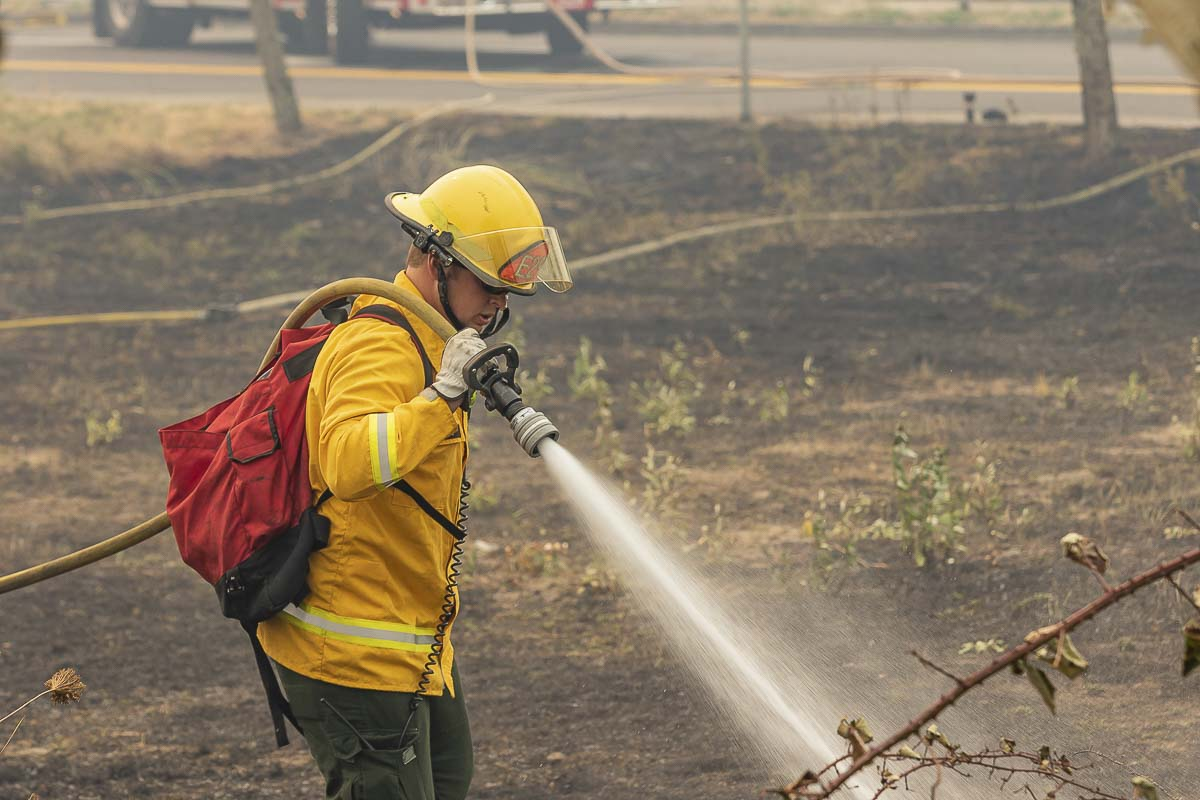 Due to extremely high temperatures and windy conditions, the Battle Ground Fire Marshal has issued a total burning ban on recreational fires within the city of Battle Ground, effective immediately. Here, a firefighter helps extinguish a fire near the Walmart in Woodland Tuesday. Photo by Mike Schultz