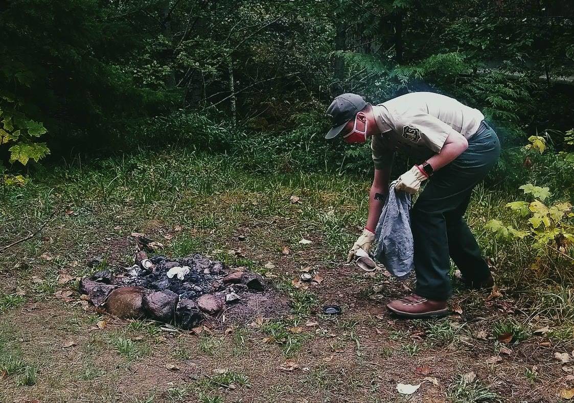 A U.S. Forest Service ranger helps pick up trash in an unimproved camping area in the Gifford Pinchot National Forest. Photo courtesy Gifford Pinchot National Forest