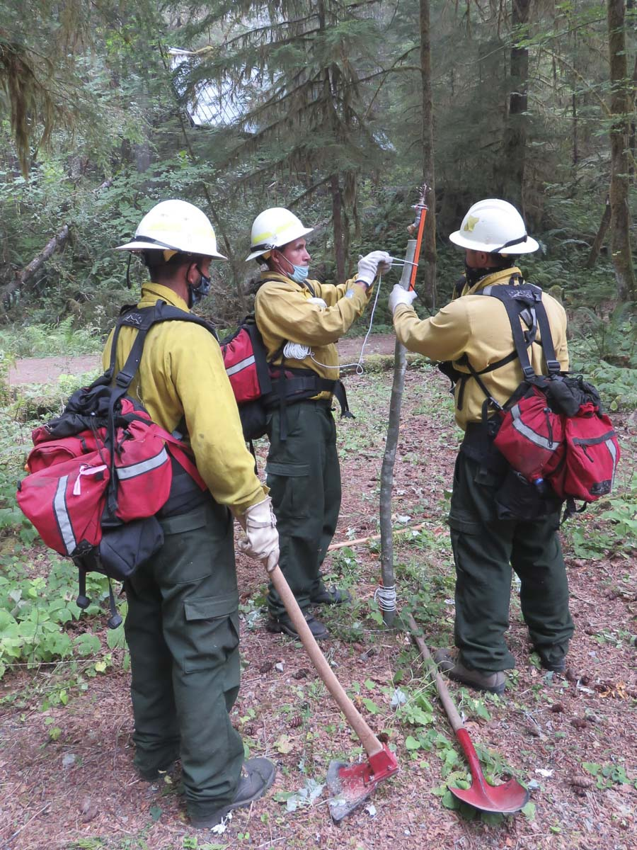 Fire crews with the Northwest Incident Management Team 12 work to install sprinklers to protect buildings at Government Mineral Springs. Photo courtesy U.S. Forest Service