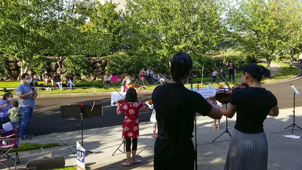 Violin students hold a recital in the driveway of teacher Clarisse Atcherson, as family members enjoy the music. Video from John Ley