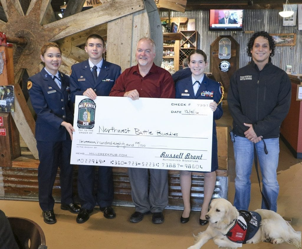 As owner of Mill Creek Pub in Battle Ground, Russell Brent was always involved in efforts to serve his community. Here, Prairie High School Air Force JROTC cadets Heather Lee, Nate Garate and the Corps Commander Nikki Wilson, Brent and combat veteran Travis Cottrell, with his Northwest Battle Buddies dog Ranger, are pictured as the group presents a check to NWBB. Photo courtesy of the Battle Ground School District