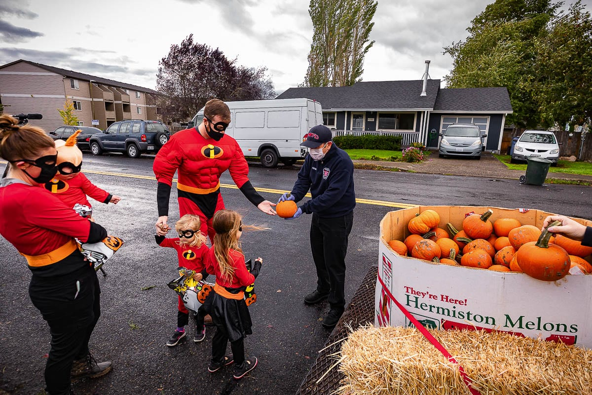 Firefighter with Camas-Washougal Fire Department, Bill Haynes, gives out pumpkins from the parade-style trailer during the festival. Photo by Mike Schultz