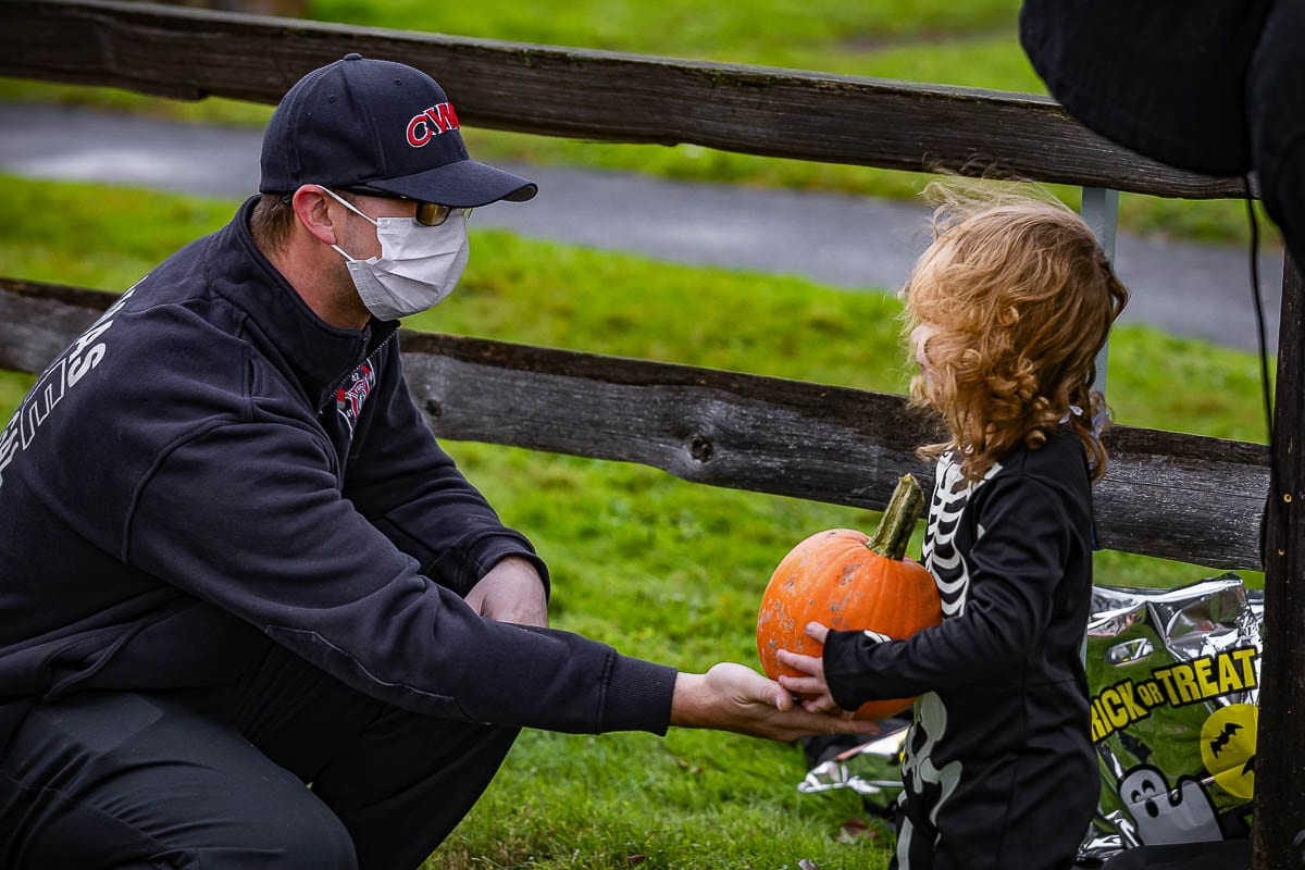 Camas-Washougal firefighter Steve Camden is shown heer handing out pumpkins during the festival. Photo by Mike Schultz