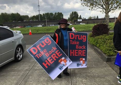 Volunteers wait outside a drug take back event in 2019. File photo