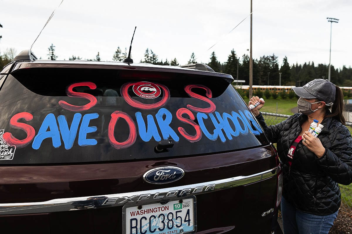 "Concerned parent Heather Wynn adds a colorful ""Save Our Schools"" message to the rear window on her vehicle. Wynn and roughly 30 other vehicles filled with Camas residents joined the rally hoping to bring attention to parents' desire to reopen Camas schools safely for in-classroom instruction. Photo by Mike Schultz"