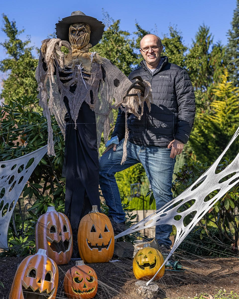 Jim Mains poses here with his 15-foot-tall Halloween scarecrow at his home on Franklin Street. Photo by Mike Schultz