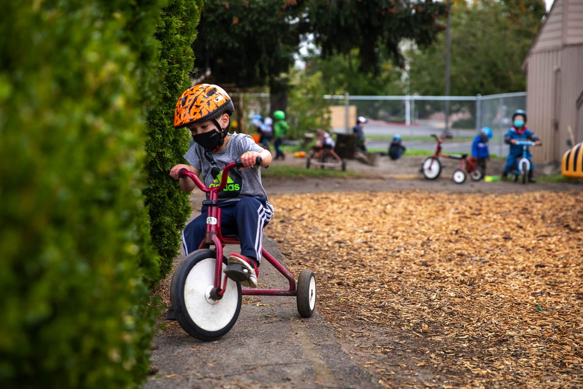 A preschooler rides a bike along the small path encircling the outdoor playground at St. Andrew Preschool in Vancouver. Photo by Jacob Granneman