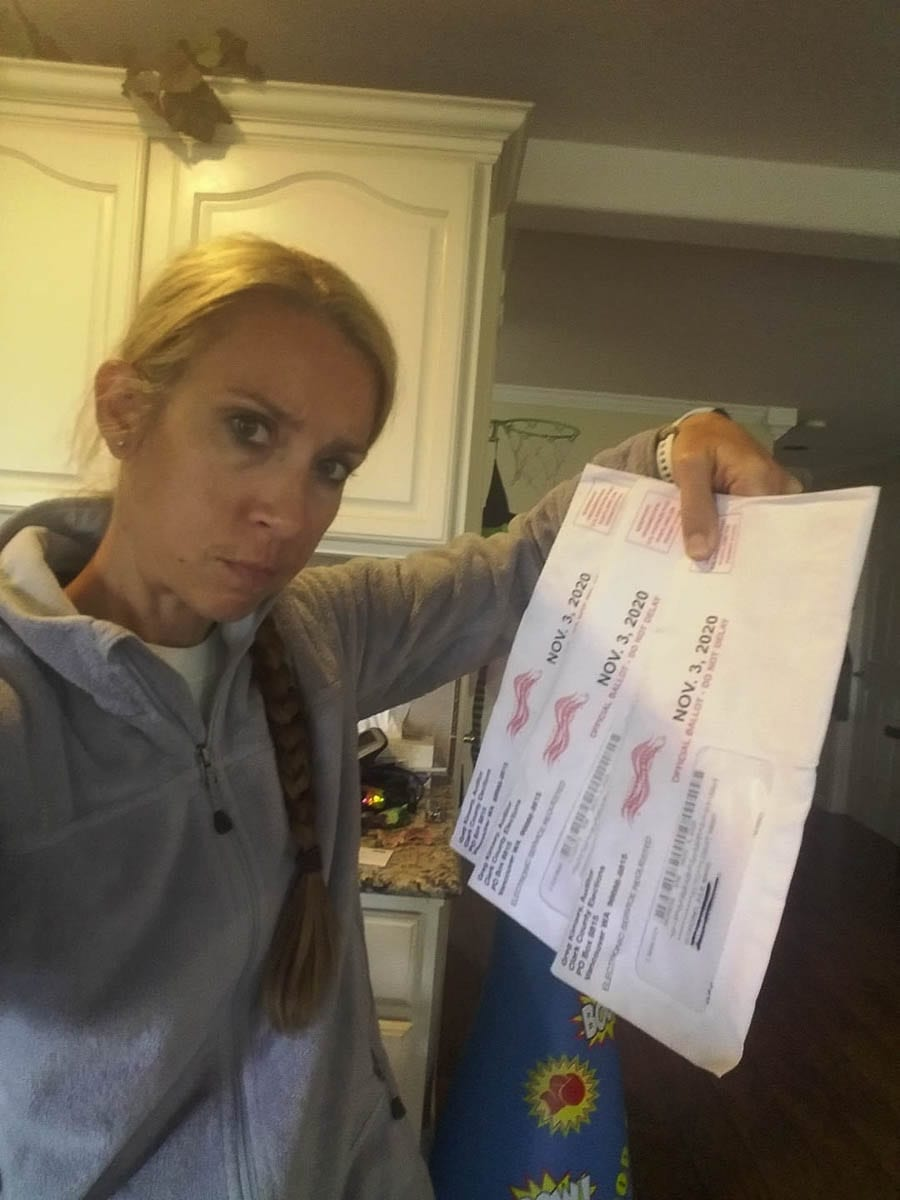 Julie Bonaci Scordino holds the three election ballots delivered by Camas police Sunday morning. Vandals broke into their neighborhood mailbox early Sunday morning, stealing mail, including the ballots. Photo Julie Bonaci Scordino