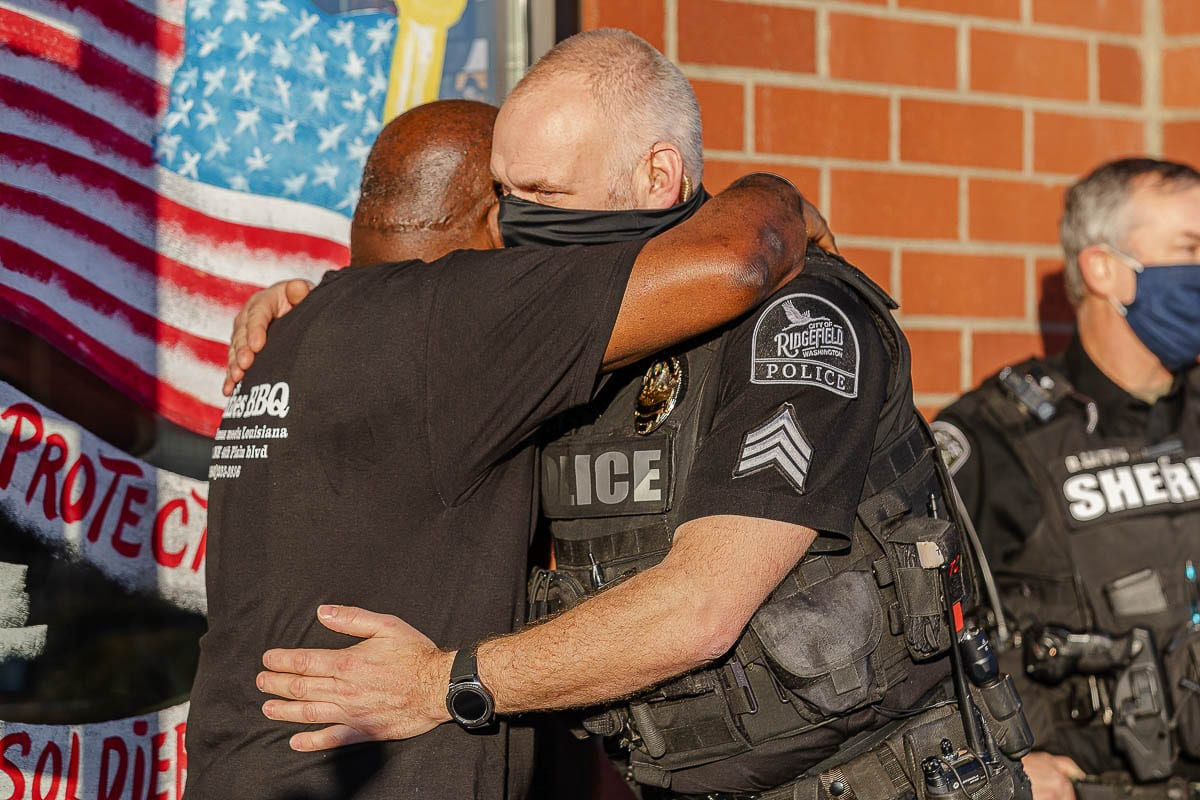 Jeff Pettit of the Ridgefield Police Department gives Charles Bibens, owner of Goldies BBQ, a hug as Bibens was surprised by a gift from Kindness 911 and law enforcement officials. Photo by Mike Schultz