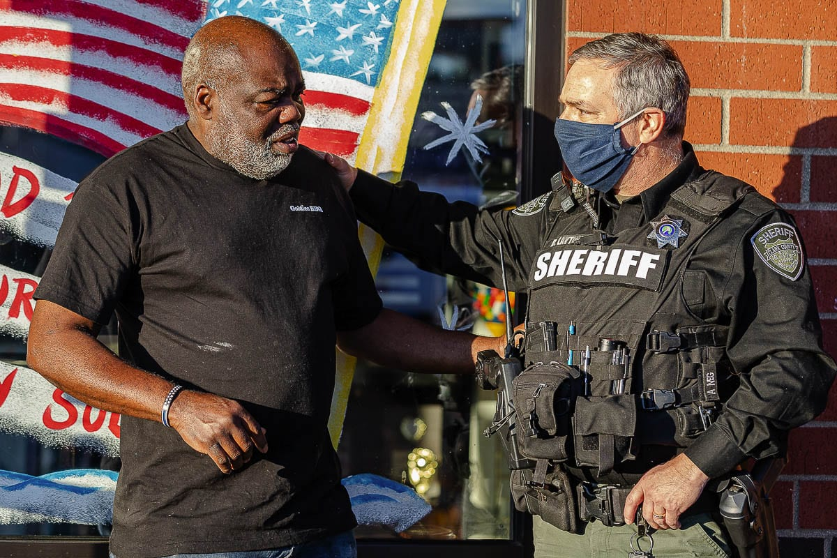 Charles Bibens, owner of Goldies BBQ, talks with Duwayne Layton of the Clark County Sheriff's Office as several law enforcement agencies helped Kindness 911 give back to Bibens. Photo by Mike Schultz