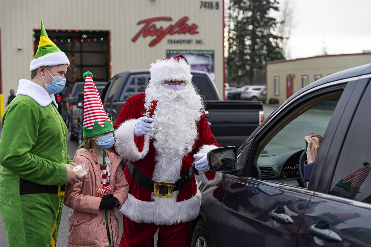 Elves Dylan Johnson and Delaney Baylous help Santa hand out treats to those waiting to pick up bicycles at the Scott Campbell Christmas Promise. Photo by Mike Schultz