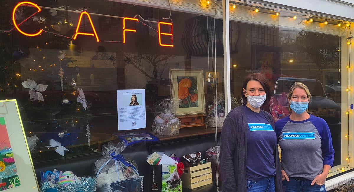 Samantha Horner (left) and Wendy DelBosque are among the organizers of a silent auction to help a Camas business owner, who has a daughter with brain cancer. The items up for auction are on display at Natalia's Cafe in downtown Camas. Photo by Paul Valencia