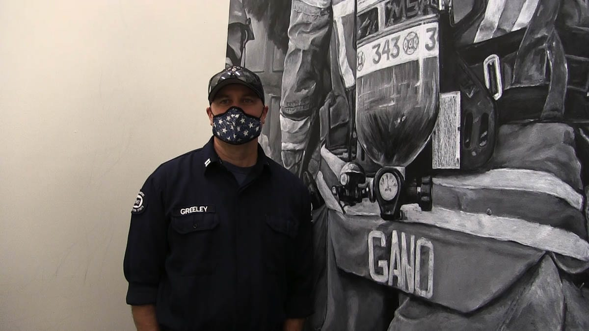 Capt. Clint Greenley stands at the base of his new 15-foot mural in Station 63. Photo courtesy of Fire District 6
