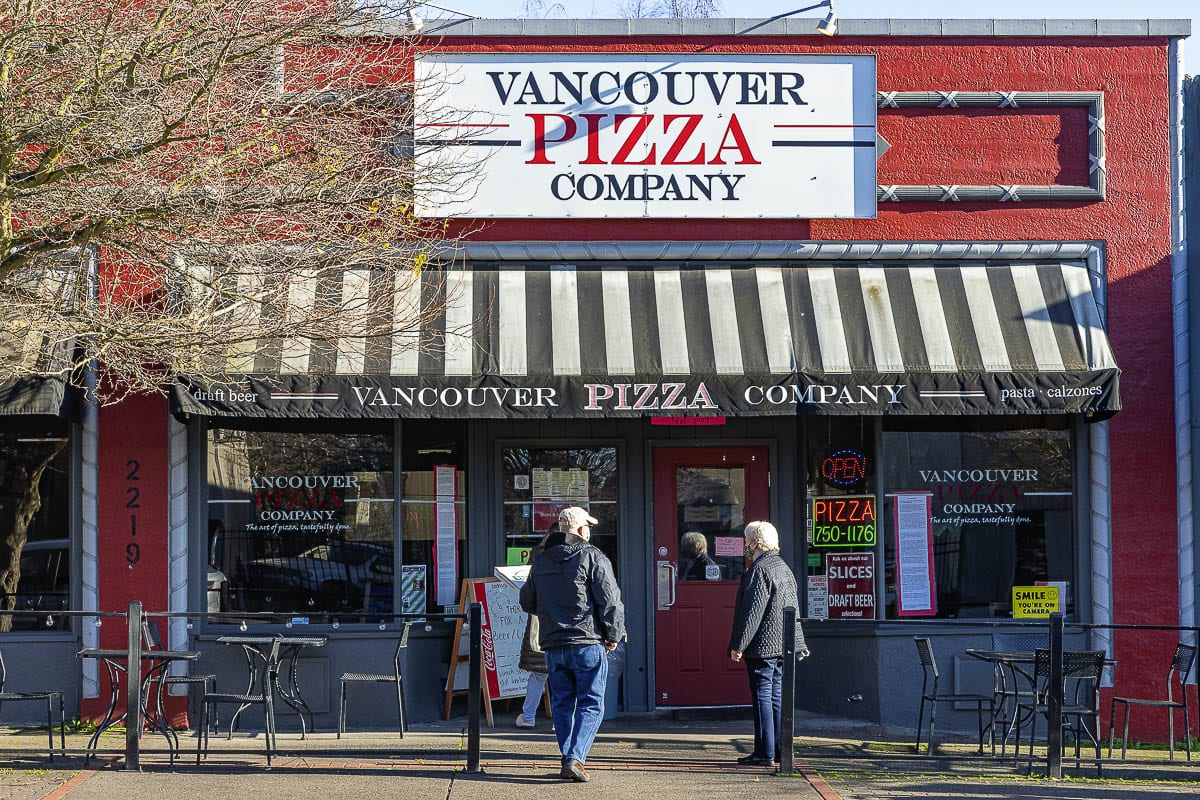 Customers wait outside of Vancouver Pizza Company on Main Street to pick up their order. The long-time Uptown Village restaurant announced they are closing permanently at the end of the year. Photo by Mike Schultz