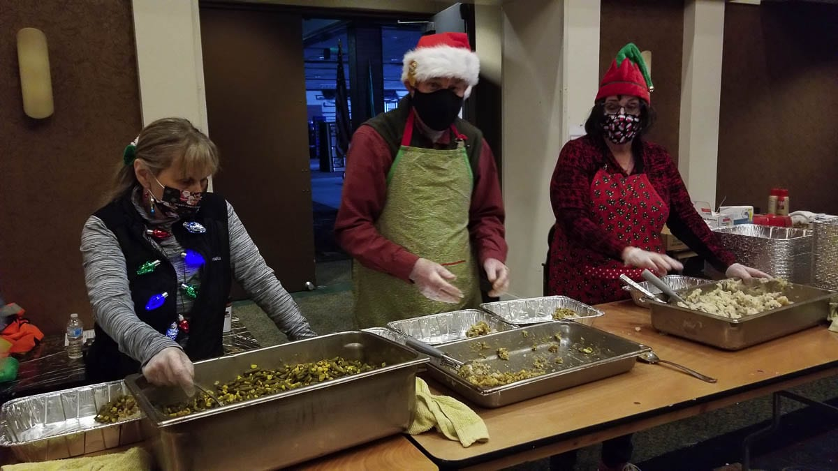 Dozens of Santa's helpers showed up Christmas morning, dishing up hot meals in take out containers that contained turkey, ham, potatoes, stuffing, gravy, green beans,a roll and an apple turnover. Photo by John Leyv Hell