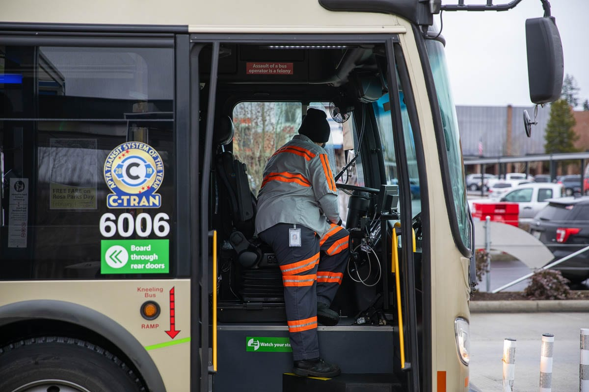 A C-TRAN worker is seen here disinfecting the driver's area on a VINE bus at the Vancouver Mall station. Photo by Jacob Granneman