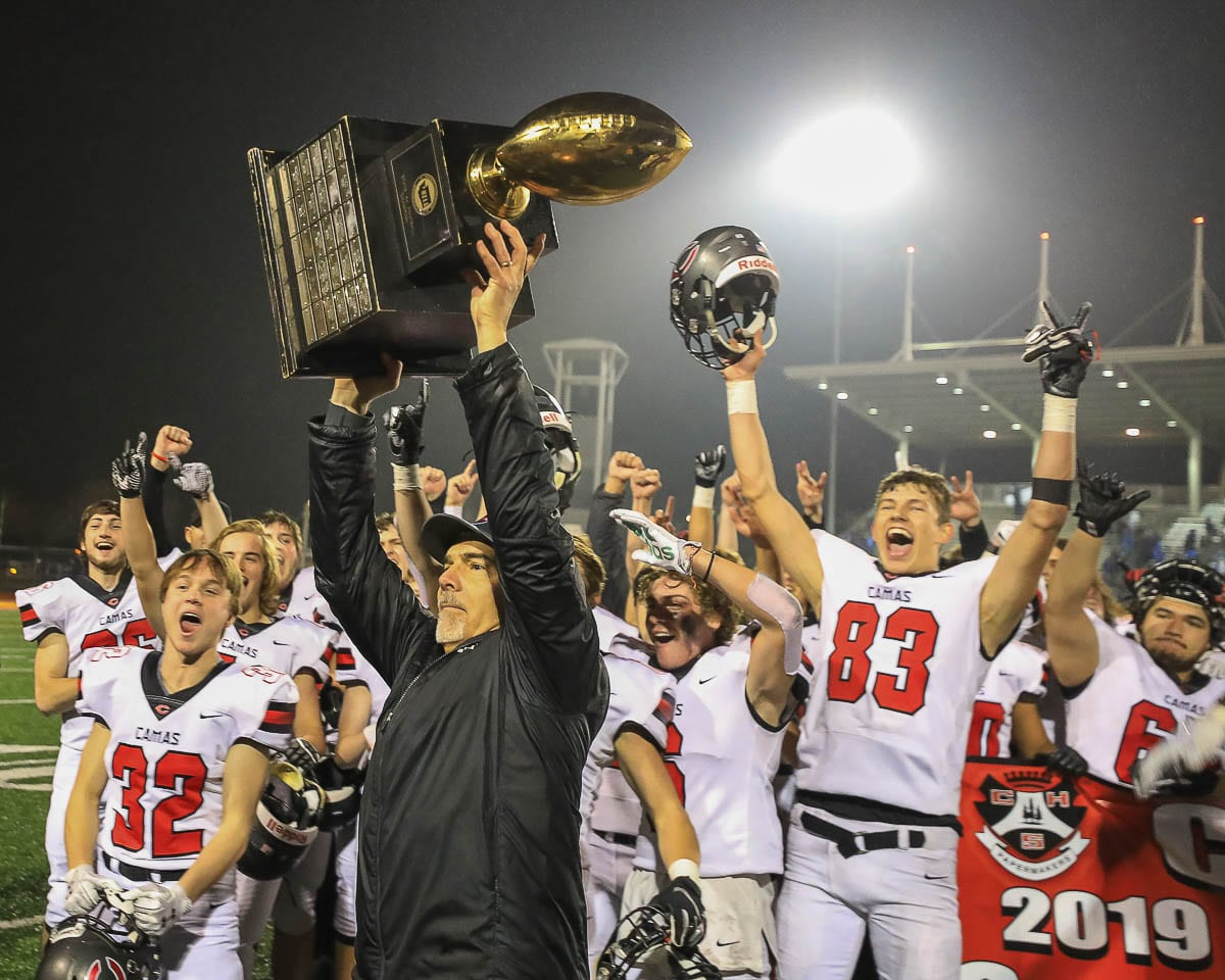 Camas coach Jon Eagle hoists the state championship trophy after the Papermakers won it all in December 2019. Football season is back after a long offseason. The 4A and 3A GSHL will start playing Feb. 26. Photo by Mike Schultz