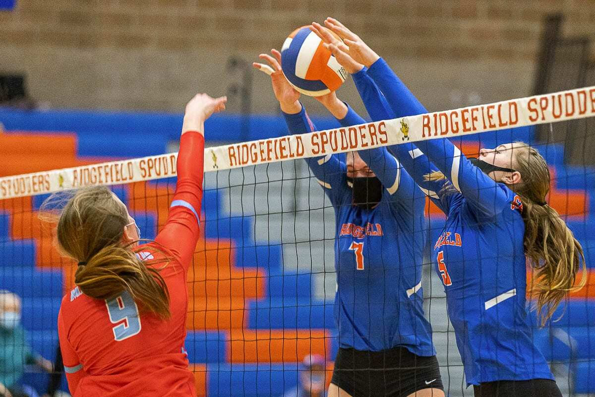 Alicia Andrew and Natalie Andrew team up to get the block for Ridgefield volleyball Tuesday. Photo by Mike Schultz