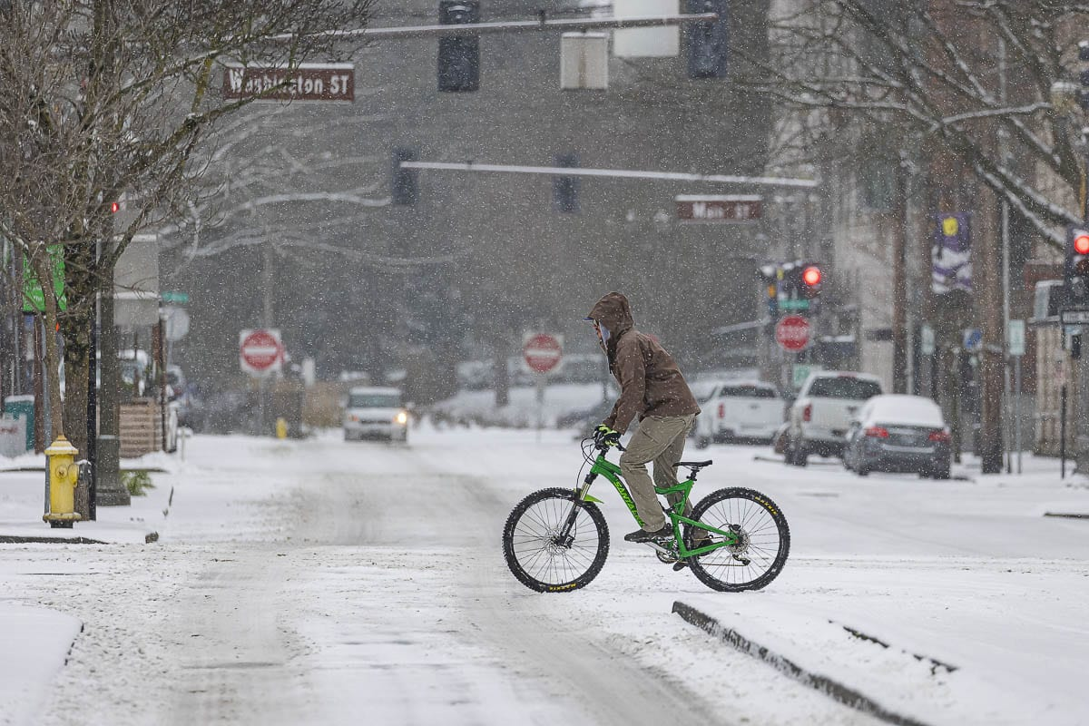 A bicyclist pedals through snowfall in downtown Vancouver on Friday morning. Photo by Mike Schultz
