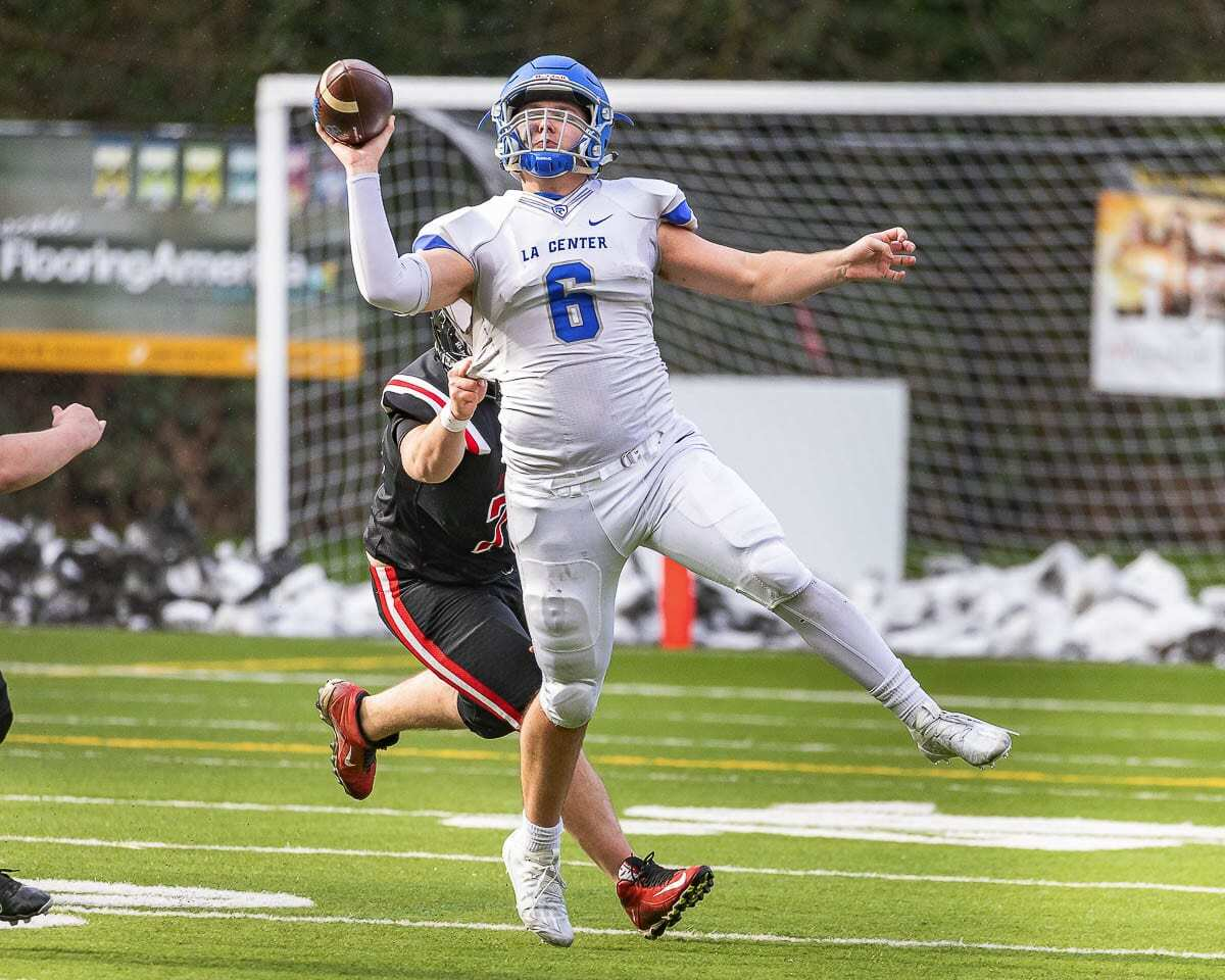 La Center quarterback Tom Lambert had to scramble before throwing this pass Saturday. No matter how he did it, it worked. He threw for a school-record seven touchdown passes in a win over Fort Vancouver. Photo by Mike Schultz