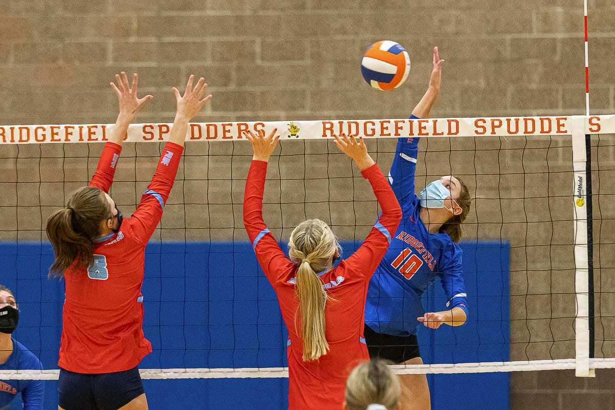 Morgan Harter of Ridgefield rises up to spike it against two Mark Morris defenders Tuesday during their volleyball match. Photo by Mike Schultz