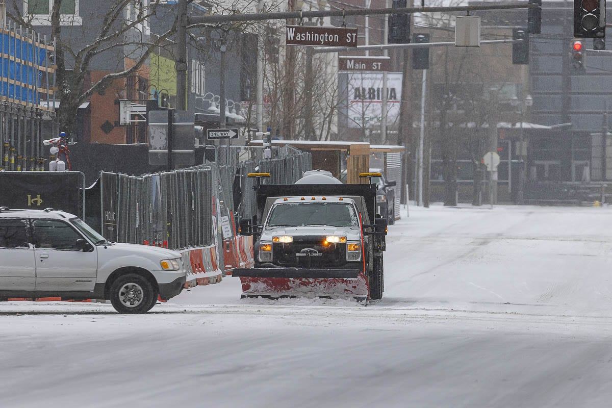 A Vancouver Public Works snow plow clears a snow-covered road downtown on Friday. Photo by Mike Schultz