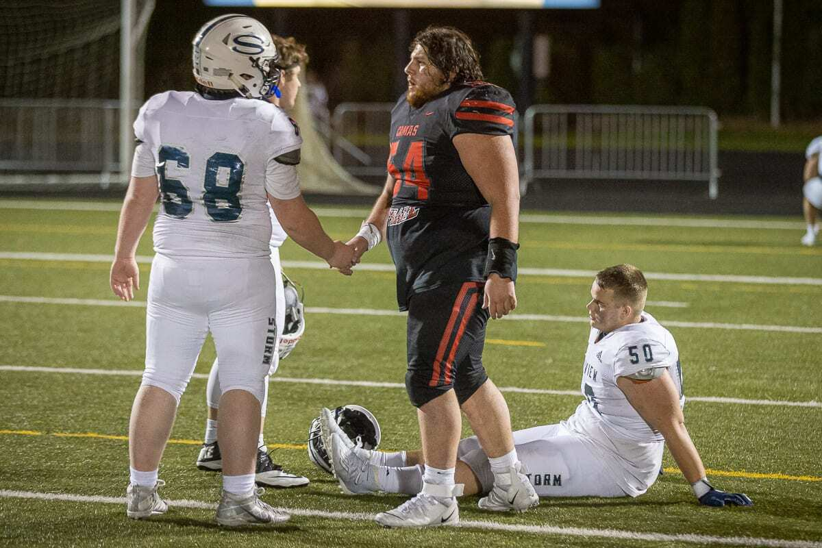 Camas senior Robert Silva (54) shakes hands with Skyview's Trenton Miller after the two teams put on a show Tuesday night. Camas prevailed 38-31 in double overtime. Photo by Mike Schultz