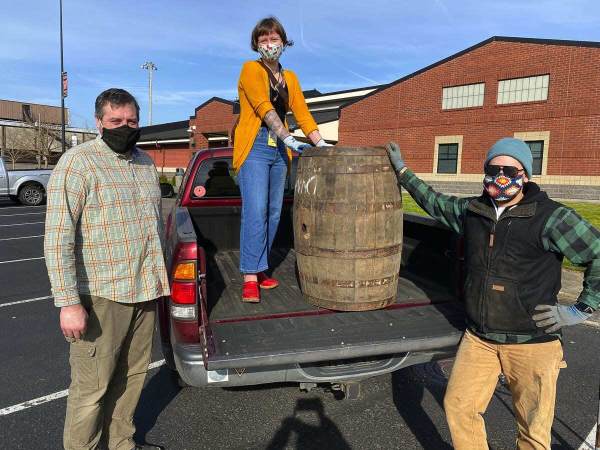 Brent Mansell, Washougal High School CTE Woods Technology teacher, and Alexandra Yost, CTE Pro Tech for the Washougal School District, and Derek Rivilo, from Logsdon Farmhouse Ales, gather to unload the four wooden barrels donated to the Washougal School District. Photo courtesy of Washougal School District