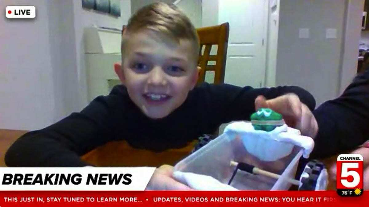 """Elijah Wilkes proudly shows his green clay figure and rubber band seatbelt in a Zoom """"news"""" report. Photo courtesy of Ridgefield School District"""