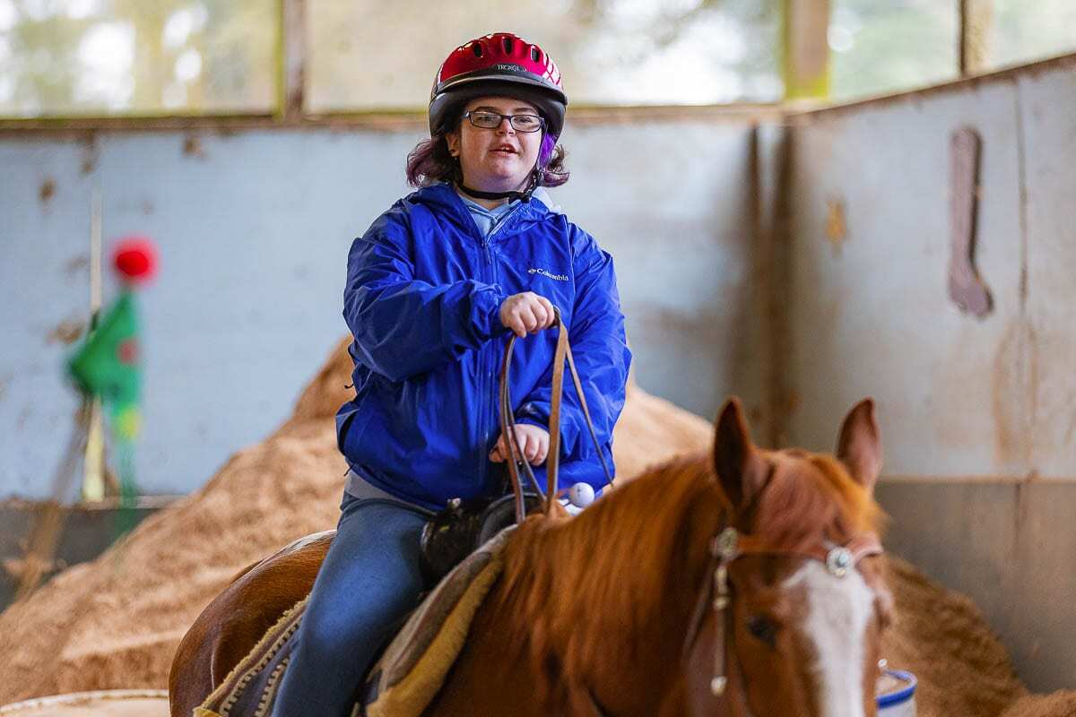 Emily Van Houten, who has special needs, is a regular rider at Healing Winds Therapeutic Riding Center. Photo by Mike Schultz