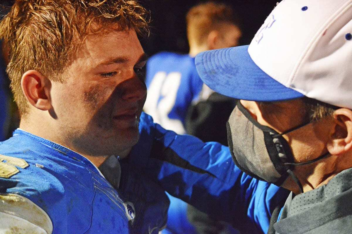 "La Center head football coach John Lambert hugs his son, Tom, after their final high school football game together. ""Life moves pretty fast,"" Lambert wrote on Twitter with pictures of Tom growing up. ""You don't stop and look around once in a while, you could miss it."" Photo by Dan Trujillo"