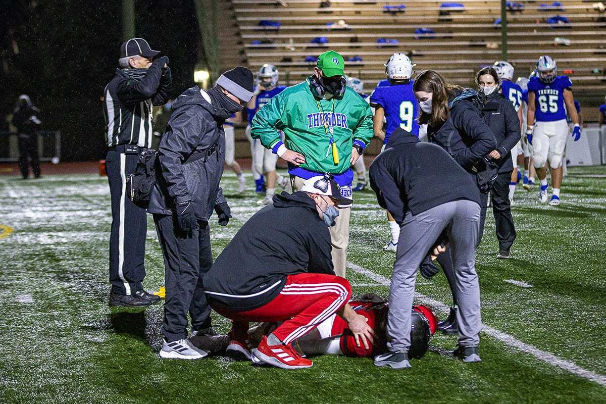 """Liam Mallory of Union, surrounded by trainers and coaches from both teams Friday, suffered a knee injury. """"The game's the game. What can you do? But I still enjoyed every single moment of it,"""" Mallory said. Photo by Mike Schultz"""