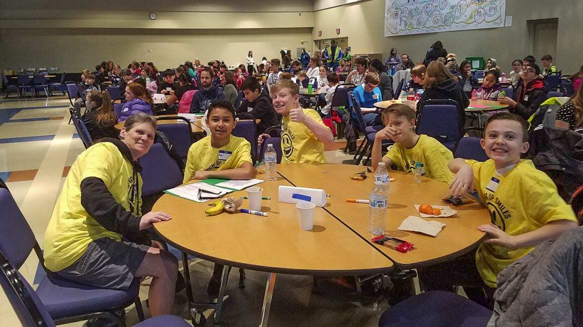 Custodian Nancy Stoy interacts with students during lunch at Lacamas Lake Elementary. Although life at the school has changed since this picture was taken, Stoy's message to protect the environment has gotten stronger. Photo courtesy of Michelle Sanow.
