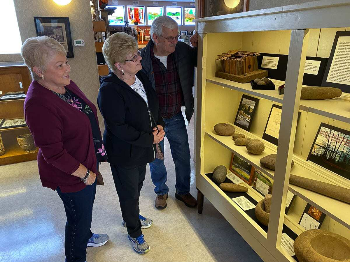 Karen Meisner, Nita Brigham and Larry Lund admire the Native American tools display. The museum is open Saturdays only from 11 a.m. to 3 p.m. Visitors will be required to wear masks. Contributed photo.