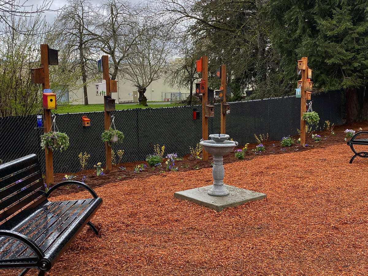 Decorated cedar bird houses, many with a Washougal High School theme, sit atop poles along an edge of the park with a bird bath and benches set nearby. Photo courtesy of Washougal School District