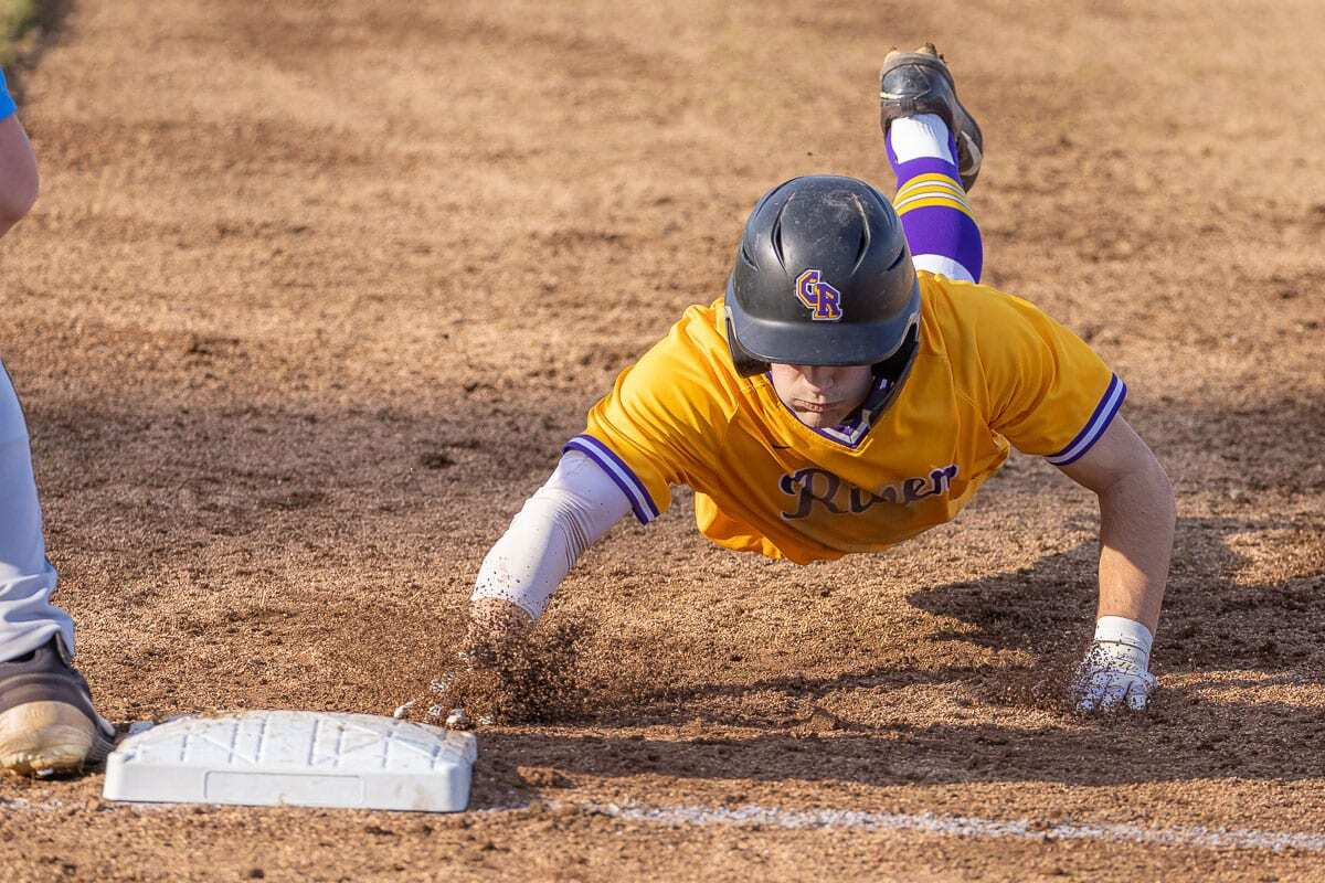 Nick Alder slides safely back to first base Wednesday during Columbia River's win over Hockinson. Photo by Mike Schultz